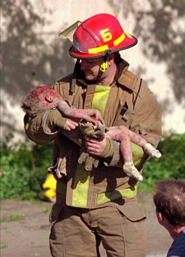 In Charles H. Porter IV's iconic photograph, OKC firefighter Chris Fields carries mortally injured Baylee Almon away from the rubble. For this photo Porter was awarded the 1996 Pulitzer Prize for Spot News Photography.