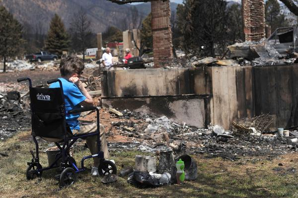 Lauretta Anzalone, Colorado Springs, looks at the ruins of her home after the fire