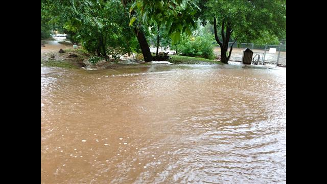 Floodwaters flow across a backyard in Boulder, Colo.