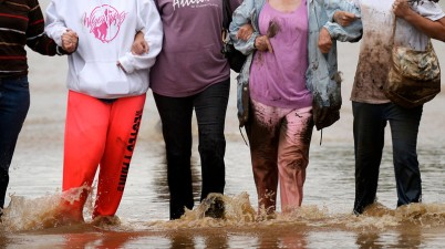 Residents, locked arm in arm, walk from their flooded homes in Evans, September 16, 2013. Massive flooding continues to hit Colorado. (Photo By RJ Sangosti/The Denver Post)