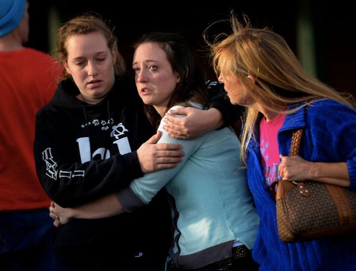 Jenni Meyers (center) 17-year-old senior is comforted by her older sister Mary Myers (left) and mom Julie as they leave Shepherd of the Hills church during a lockdown when a student carried a shotgun into Arapahoe High School and opened fire Friday, wounding two fellow students before apparently himself. (Photo: Joe Amon/The Denver Post)