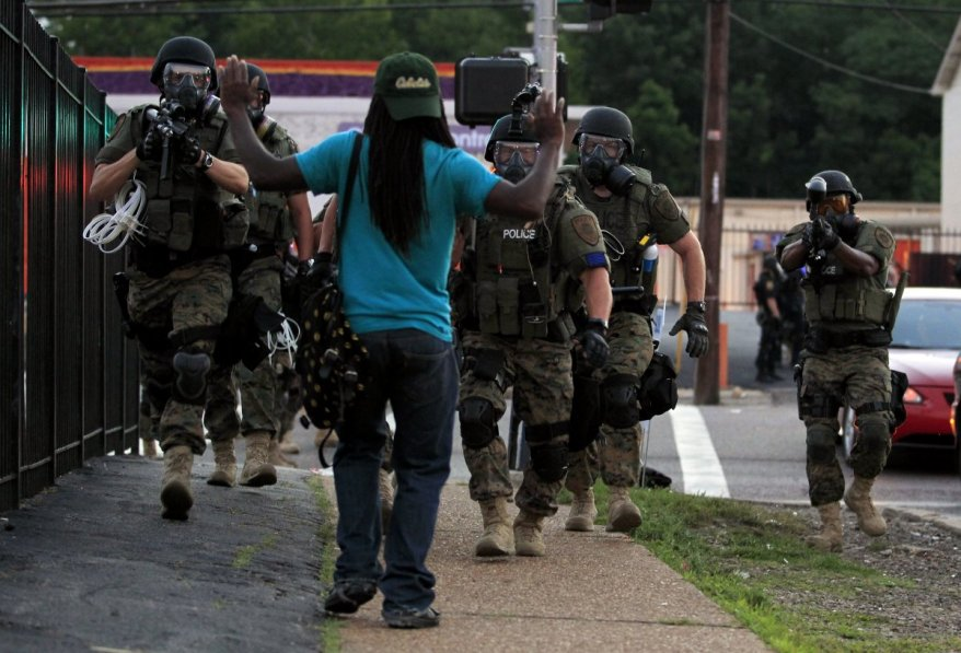 """An unarmed black man, in the """"hands up, don't shoot"""" pose adopted by Ferguson demonstrators, faces the heavily armed and armored police. (AP photo/Jeff Roberson)"""